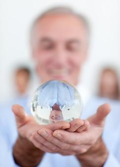 Homem de negócios sênior segurando uma bola de cristal