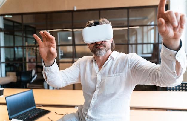 Homem de negócios sênior sentado em seu escritório e usando realidade mista para desenvolver um novo projeto