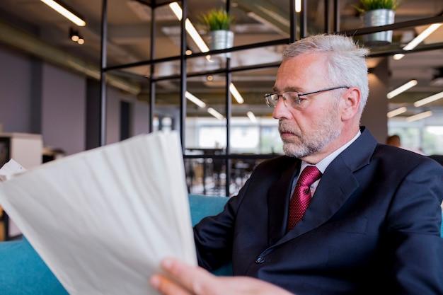 Homem de negócios sênior, sentado lendo jornal no escritório