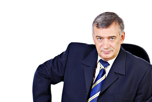 Homem de negócios sênior sério representativo sentado na cadeira.