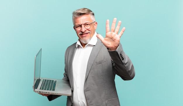 Homem de negócios sênior sorrindo e parecendo amigável, mostrando o número cinco ou quinto com a mão para a frente, em contagem regressiva