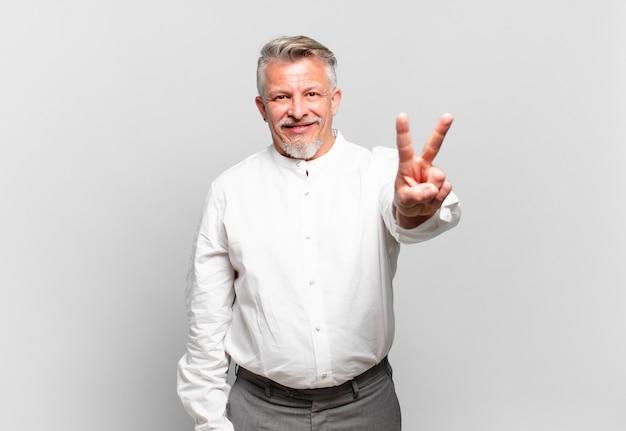 Homem de negócios sênior sorrindo e parecendo feliz, despreocupado e positivo, gesticulando vitória ou paz com uma das mãos