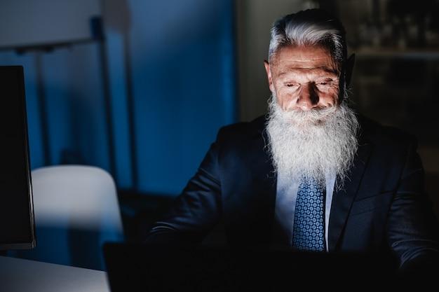 Homem de negócios sênior trabalhando à noite no escritório da empresa fintech - foco no rosto