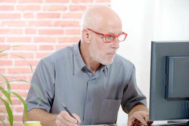 Homem de negócios sênior trabalhando no computador
