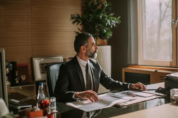 Homem de negócios sênior trabalhando no escritório moderno