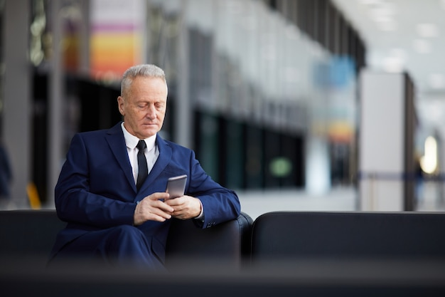 Homem de negócios sênior usando smartphone no lobby
