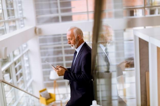 Homem de negócios sênior usando tablet digital no escritório