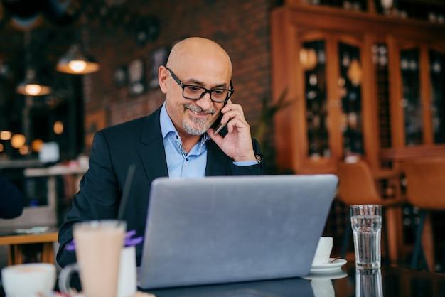 Homem de negócios sênior usando telefone inteligente e laptop enquanto está sentado no café