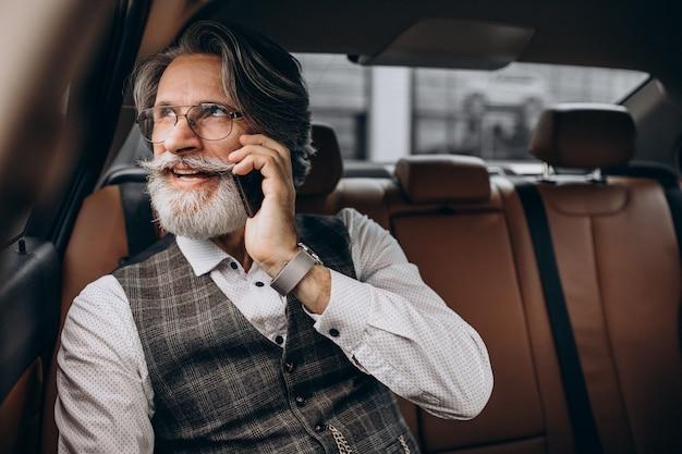 Homem de negócios sentado em seu carro no banco traseiro