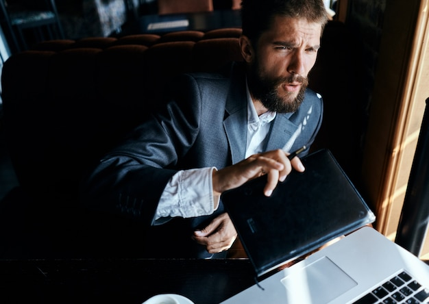 Homem de negócios sentado em um café em frente a um laptop com uma xícara de café trabalho tecnologia estilo de vida