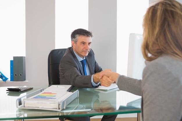 Homem de negócios sério, apertando a mão do entrevistado