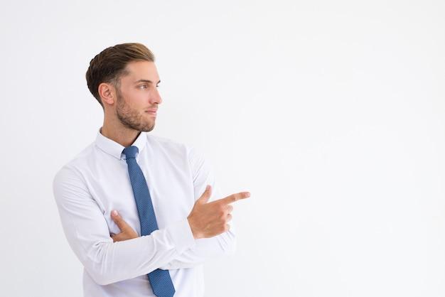 Homem de negócios sério apontando dedo lado