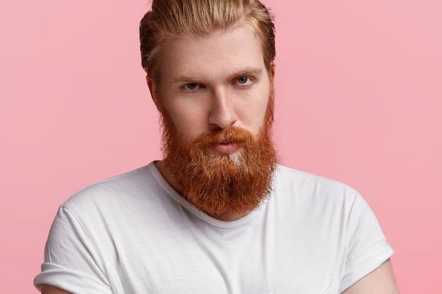 Homem de negócios sério bonito com barba ruiva espessa, pele perfeita, olhando diretamente para a câmera com olhar misterioso