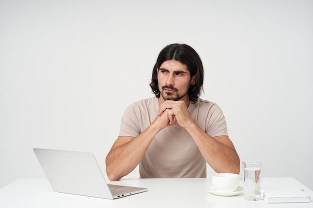 Homem de negócios sério, cara pensativo com barba e cabelo preto. conceito de escritório. sentado no local de trabalho. apoie o queixo nos braços. observando à esquerda no espaço da cópia, isolado sobre a parede branca