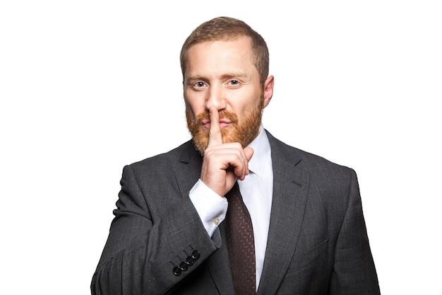 Homem de negócios sério com o dedo nos lábios fazendo gesto de silêncio. isolado no fundo branco, olhando para a câmera.