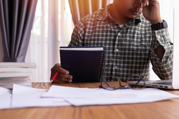 Homem de negócios sério com relatório comercial na tabela de madeira.