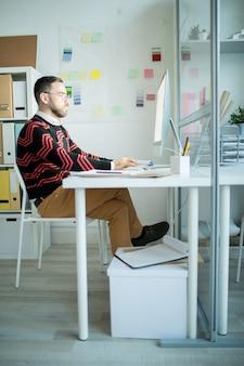 Homem de negócios sério com roupa elegante trabalhando sozinho em offic