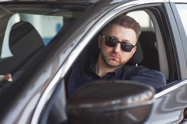 Homem de negócios sério com roupas oficiais experimentando seu novo carro em salão de automóveis