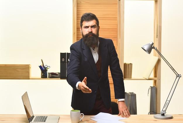 Homem de negócios sério dando boas-vindas ao retrato de aperto de mão de um homem de negócios barbudo considerável