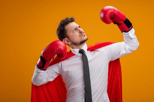 Homem de negócios sério de super-herói confiante com capa vermelha e luvas de boxe levantando as mãos, mostrando força e coragem em pé sobre um fundo laranja