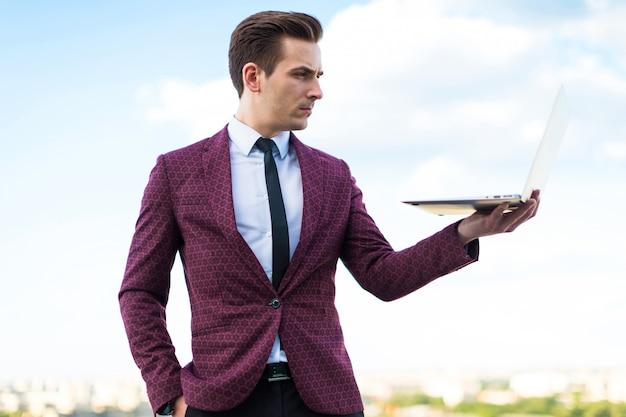 Homem de negócios sério de terno vermelho e camisa com gravata fica no telhado com o laptop