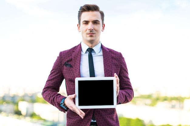 Homem de negócios sério de terno vermelho e camisa com gravata fica no telhado com tablet vazio