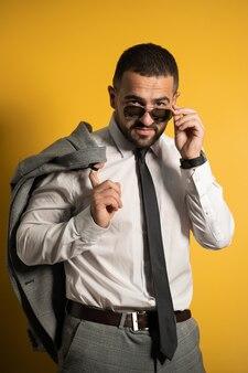Homem de negócios sério e barbudo vestido em suíte acinzentada posando segurando sua jaqueta no ombro pendurando-a atrás, olhando baixando os óculos de sol isolados no fundo amarelo.