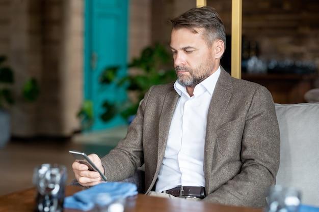 Homem de negócios sério e elegante em trajes formais, sentado no sofá em um restaurante ou café na hora do almoço e rolando no smartphone