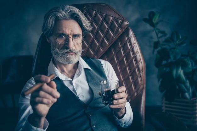 Homem de negócios sério elegante bebendo álcool e fumando cigarro no escritório