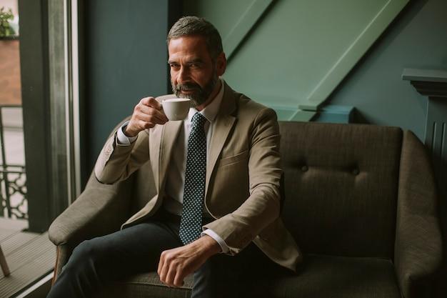 Homem de negócios sério elegante considerável que senta-se na poltrona e que guarda o copo do café.
