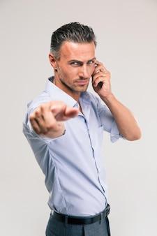 Homem de negócios sério falando ao telefone e apontando para a câmera isolada