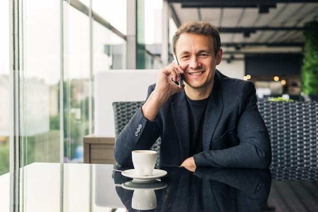 Homem de negócios sério falando ao telefone em restaurante