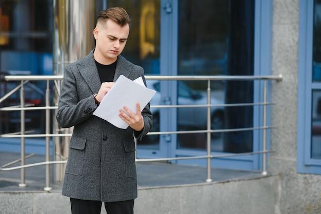 Homem de negócios sério lendo documentos na rua