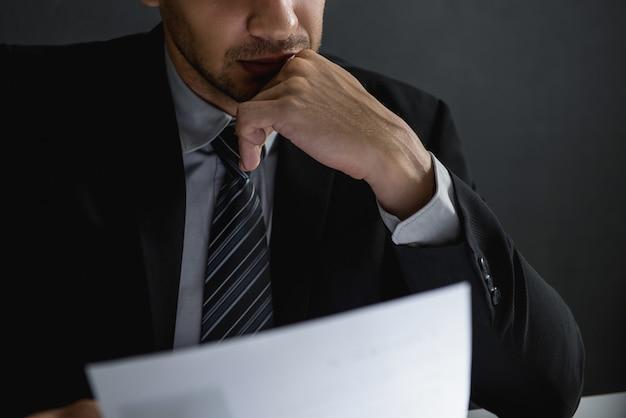 Homem de negócios sério lendo o documento e ponderando