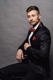 Homem de negócios sério no elegante terno trespassado, sentado em uma cadeira no fundo cinza studio