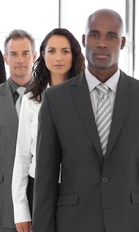 Homem de negócios sério olhando a câmera com o grupo em segundo plano