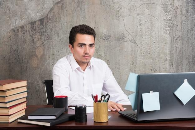 Homem de negócios sério olhando a câmera para a mesa do escritório.