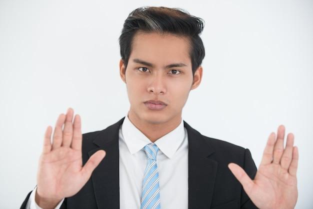 Homem de negócios sério que mostra um gesto de rendição
