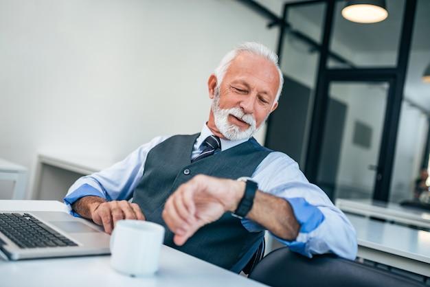 Homem de negócios sério que olha o relógio de pulso que verifica o tempo.