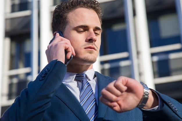 Homem de negócios sério que verifica o tempo que fala no telefone.