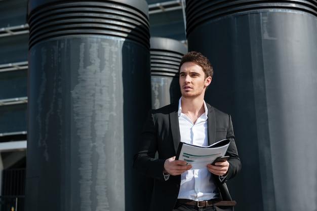 Homem de negócios sério segurando documentos