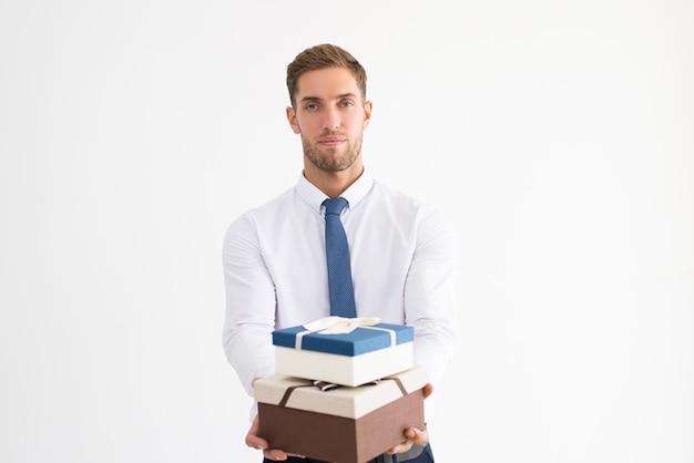 Homem de negócios sério segurando duas caixas de presente com laços de fita