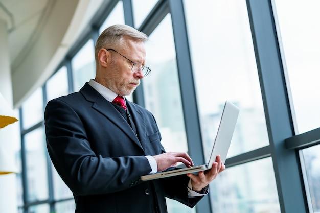 Homem de negócios sério sênior em pé perto da janela com vista panorâmica da cidade. laptop nas mãos.