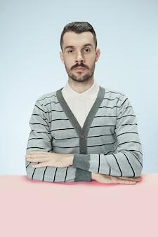 Homem de negócios sério sentado à mesa no fundo azul do estúdio. o retrato em estilo minimalista