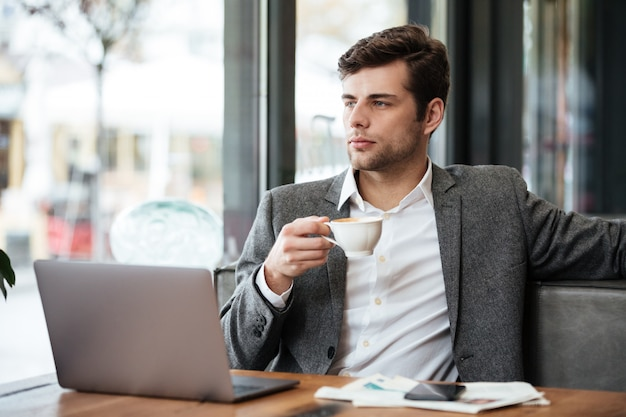 Homem de negócios sério sentado junto à mesa no café com o computador portátil enquanto bebe café e olhando para a janela