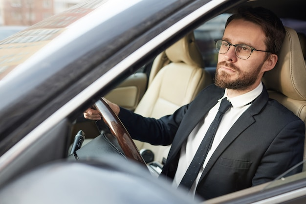 Homem de negócios sério sentado no carro