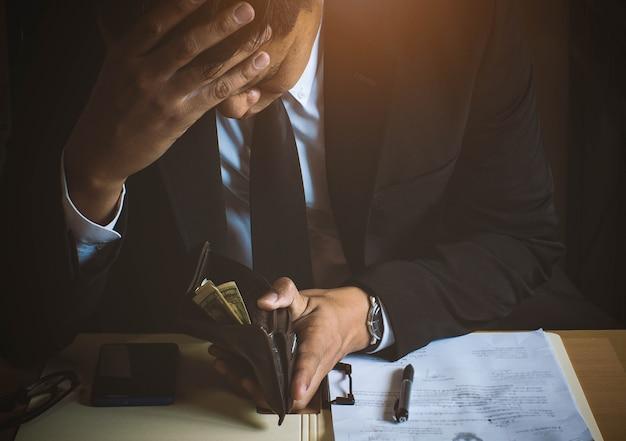 Homem de negócios sério sentou-se estressado sobre dinheiro em billfold.low estilo chave