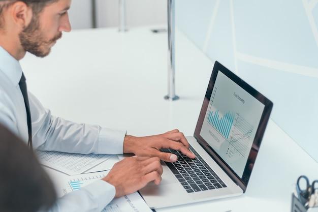 Homem de negócios sério trabalhando em seu laptop no escritório