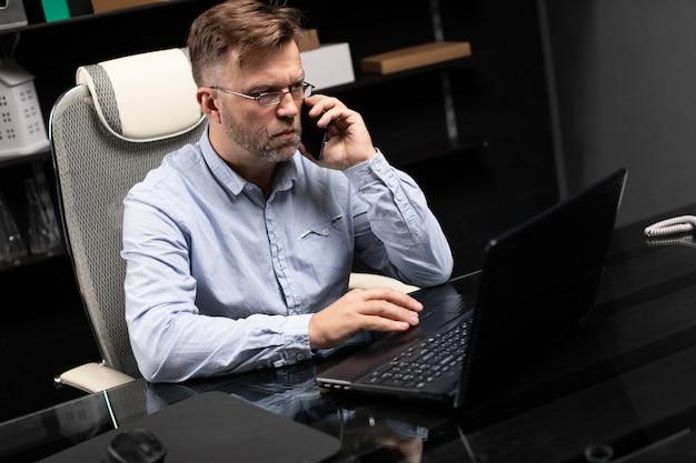 Homem de negócios sério trabalhando em um laptop e falando em um telefone celular