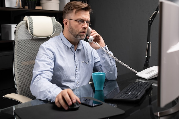 Homem de negócios sério trabalhando no escritório, na mesa do computador e falando de telefone fixo